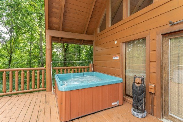 Hot tub on a covered deck at Aw Paw's Place, a 1-bedroom cabin rental located in Pigeon Forge