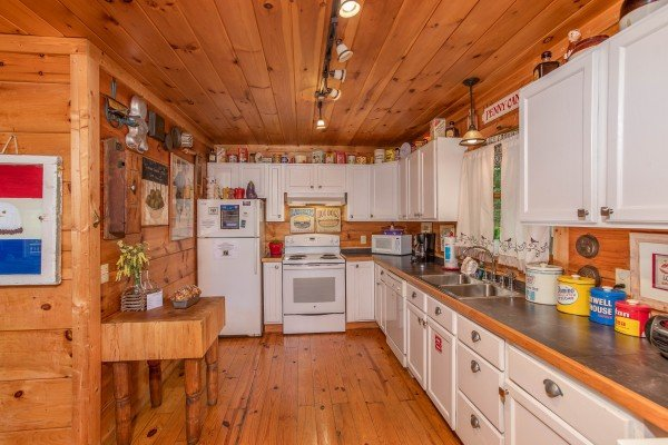 Kitchen with white cabinets and appliances at Aw Paw's Place, a 1-bedroom cabin rental located in Pigeon Forge
