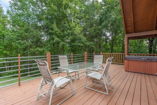 Outdoor dining on the deck with seating for four at Aw Paw's Place, a 1-bedroom cabin rental located in Pigeon Forge