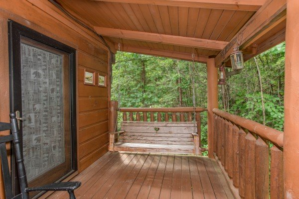 Porch swing on a covered deck at Aw Paw's Place, a 1-bedroom cabin rental located in Pigeon Forge