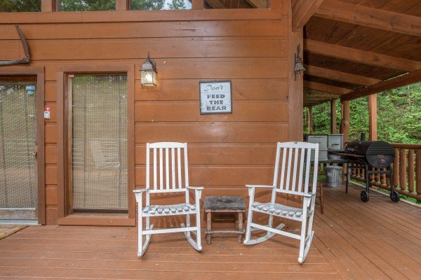 White rocking chairs on a covered deck at Aw Paw's Place, a 1-bedroom cabin rental located in Pigeon Forge