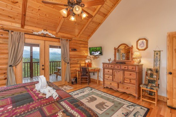 Dresser with mirror, writing desk, TV, and deck access in a bedroom at I Do Love Views, a 3 bedroom cabin rental located in Pigeon Forge
