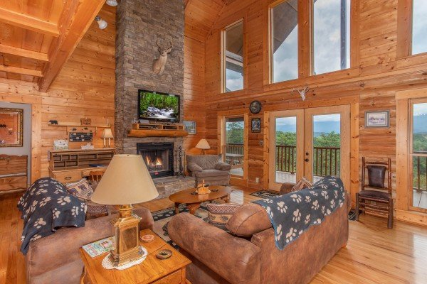 Living room with fireplace, TV, and large windows for lots of light at I Do Love Views, a 3 bedroom cabin rental located in Pigeon Forge