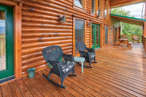 Wicker rocking chairs on the covered deck at I Do Love Views, a 3 bedroom cabin rental located in Pigeon Forge