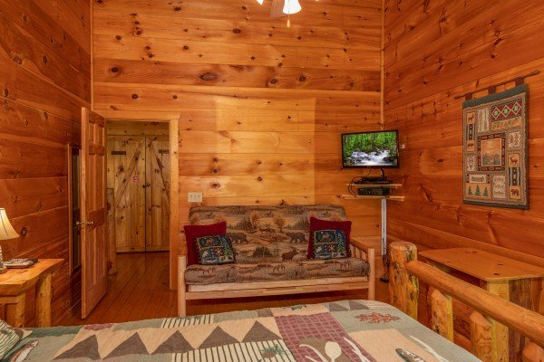 Futon in the loft bedroom with a tv at Misty Mountain Escape, a 2 bedroom cabin rental located in Gatlinburg