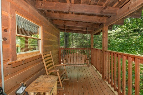 Swing and rocking chair on a covered porch at Misty Mountain Escape, a 2 bedroom cabin rental located in Gatlinburg