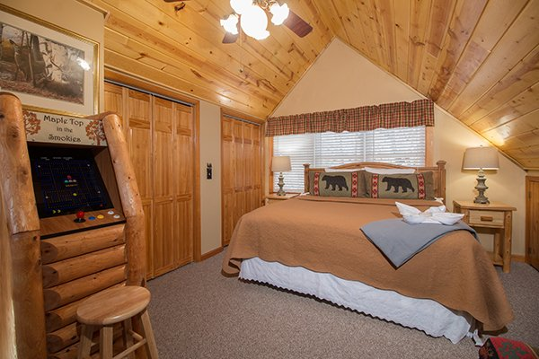 Loft bedroom with a king bed and arcade game at Maple Top in the Smokies, a 3 bedroom cabin rental located in Pigeon Forge