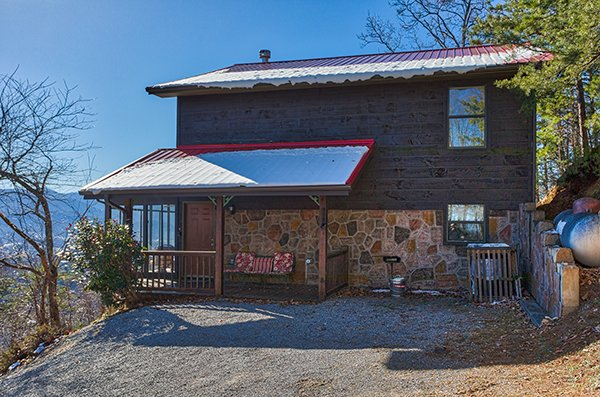 Exterior view from a gravel parking area at Alone at the Top, a 3 bedroom cabin rental located in Pigeon Forge
