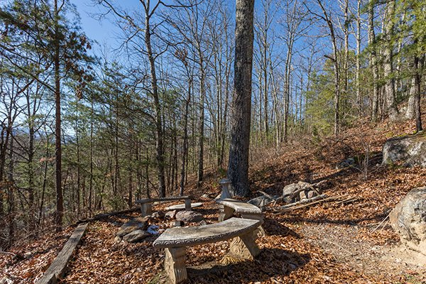 Fire pit with bench seating at Alone at the Top, a 3 bedroom cabin rental located in Pigeon Forge