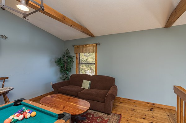 Sofa in the game room loft at Alone at the Top, a 3 bedroom cabin rental located in Pigeon Forge