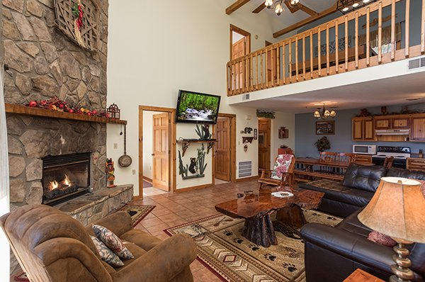 Living room with stone fireplace and television at Alone at the Top, a 3 bedroom cabin rental located in Pigeon Forge