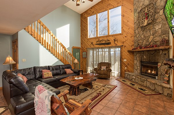 Living room with sectional sofa and stone fireplace at Alone at the Top, a 3 bedroom cabin rental located in Pigeon Forge