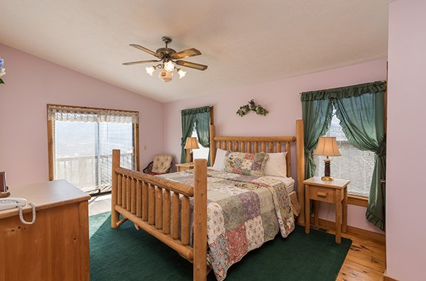 Bedroom with king sized log bed with deck access at Alone at the Top, a 3 bedroom cabin rental located in Pigeon Forge