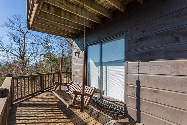 Porch swing on a covered deck at Alone at the Top, a 3 bedroom cabin rental located in Pigeon Forge