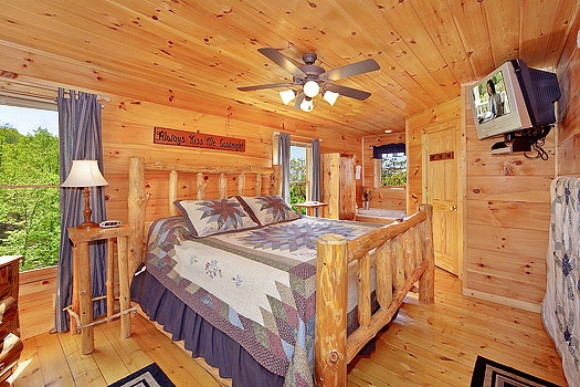 Main floor bedroom with king sized bed on custom log frame at Bearly Makin' it, a 1-bedroom cabin rental located in Gatlinburg