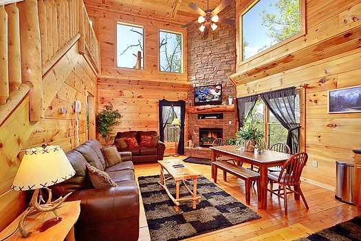 Stone fireplace surrounding by sofas at Bearly Makin' it a 1-bedroom cabin rental located in Gatlinburg