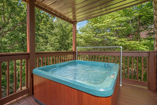 Hot tub on a covered deck surrounded by trees at Hickory Hideaway, a 3-bedroom cabin rental located in Pigeon Forge