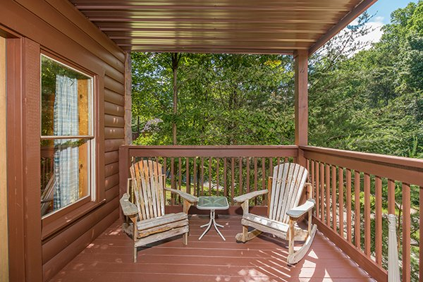 Two Adirondack chairs on a covered deck at Hickory Hideaway, a 3-bedroom cabin rental located in Pigeon Forge