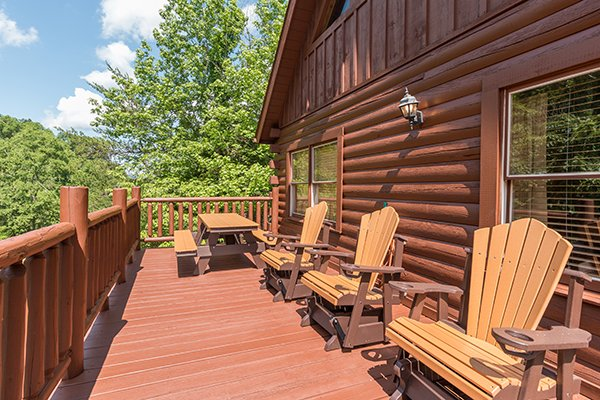 Three gliding rockers and a picnic table on the deck at Hickory Hideaway, a 3-bedroom cabin rental located in Pigeon Forge