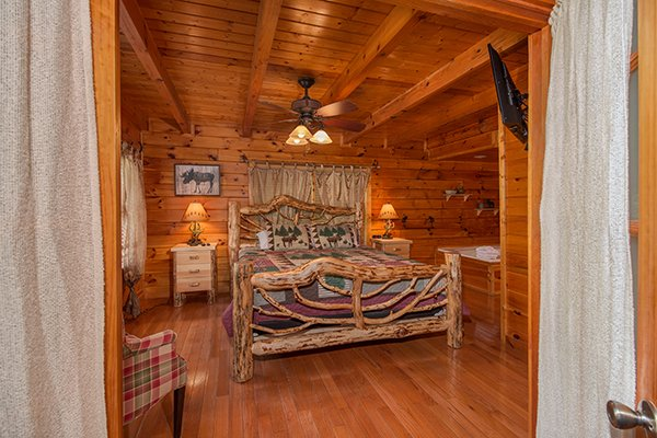 Bedroom with a custom log bed at Hickory Hideaway, a 3-bedroom cabin rental located in Pigeon Forge