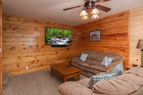 Large wall-mounted TV and sleeper sofa in the game room at Hickory Hideaway, a 3-bedroom cabin rental located in Pigeon Forge