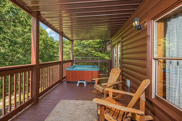 Hot tub on a covered deck and two Adirondack rockers at Hickory Hideaway, a 3-bedroom cabin rental located in Pigeon Forge