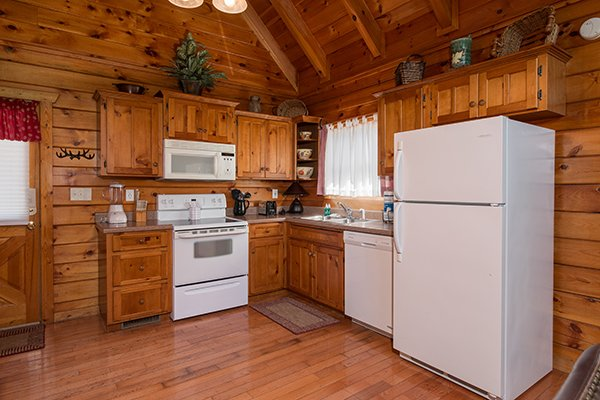 Kitchen with white appliances at Hickory Hideaway, a 3-bedroom cabin rental located in Pigeon Forge