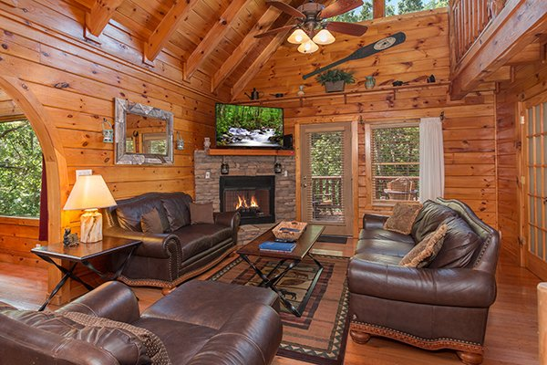 Living room with vaulted ceiling, TV, and fireplace at Hickory Hideaway, a 3-bedroom cabin rental located in Pigeon Forge