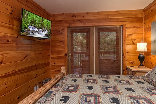 Bedroom with patio access and TV in the lower level at Hickory Hideaway, a 3-bedroom cabin rental located in Pigeon Forge