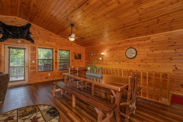Dining table with chairs and bench seating at Hawk's Heart Lodge, a 3 bedroom cabin rental located in Pigeon Forge