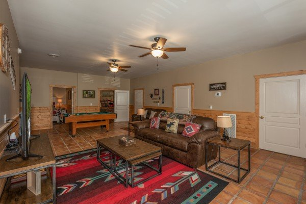 Sofa and TV in a living room with a pool table at Hawk's Heart Lodge, a 3 bedroom cabin rental located in Pigeon Forge