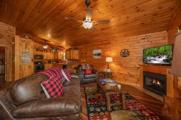 Living room with fireplace and TV next to the open kitchen at Hawk's Heart Lodge, a 3 bedroom cabin rental located in Pigeon Forge