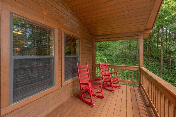 Red rocking chairs on a covered porch at Hawk's Heart Lodge, a 3 bedroom cabin rental located in Pigeon Forge