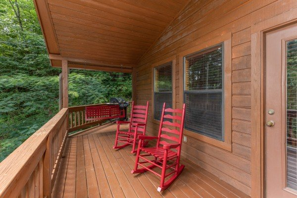 Red rocking chairs and a porch swing on a covered porch at Hawk's Heart Lodge, a 3 bedroom cabin rental located in Pigeon Forge