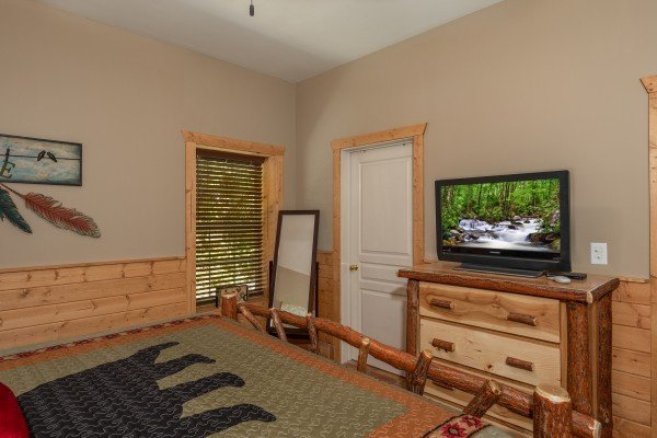 Dresser, mirror, and tv in a bedroom at Hawk's Heart Lodge, a 3 bedroom cabin rental located in Pigeon Forge