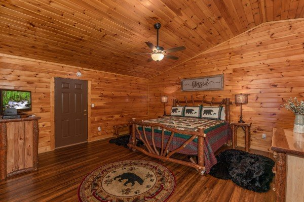 Bedroom with a log bed, dressers, and a TV at Hawk's Heart Lodge, a 3 bedroom cabin rental located in Pigeon Forge