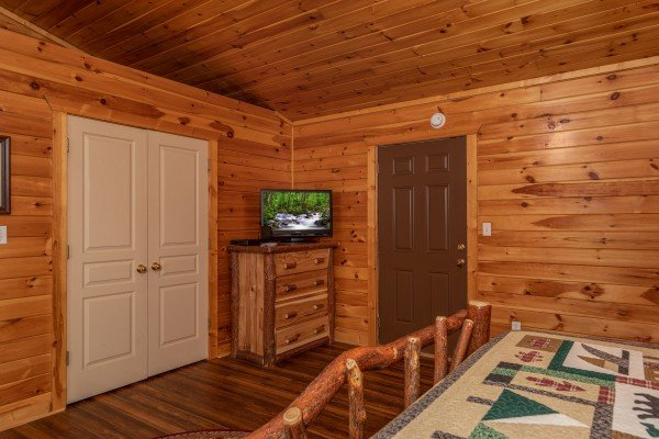 Bedroom with a dresser and TV at Hawk's Heart Lodge, a 3 bedroom cabin rental located in Pigeon Forge