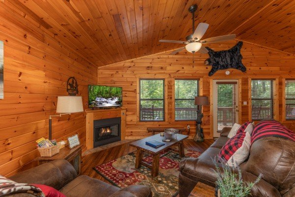 Vaulted living room with fireplace and TV at Hawk's Heart Lodge, a 3 bedroom cabin rental located in Pigeon Forge