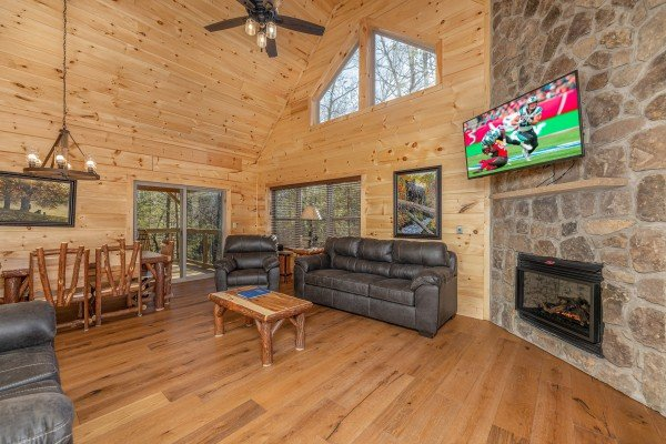 Living room and dining room with fireplace & tv at Bessy Bears Cabin, a 2 bedroom cabin rental located inGatlinburg