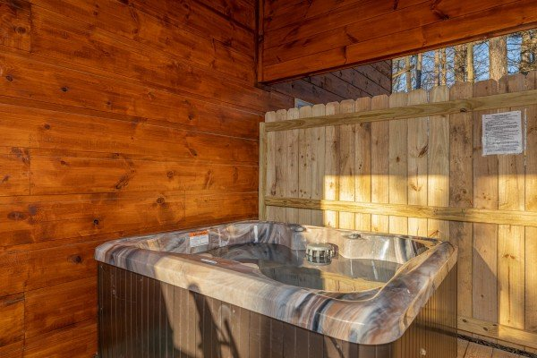 Hot tub on a covered deck with privacy fence at Bessy Bears Cabin, a 2 bedroom cabin rental located inGatlinburg