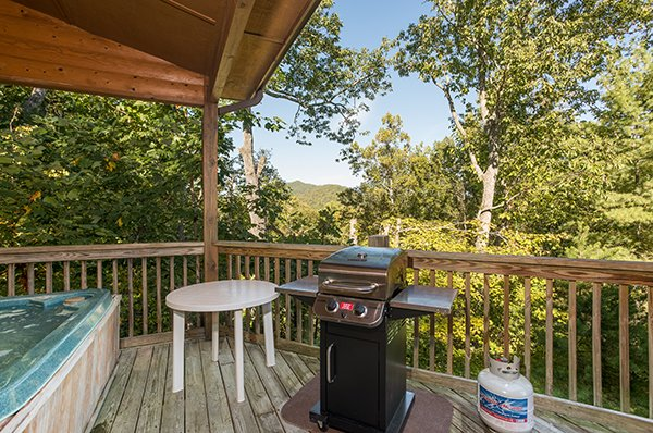 Grill on a covered deck at Mountain Valley Hideaway, a 2 bedroom cabin rental located in Pigeon Forge