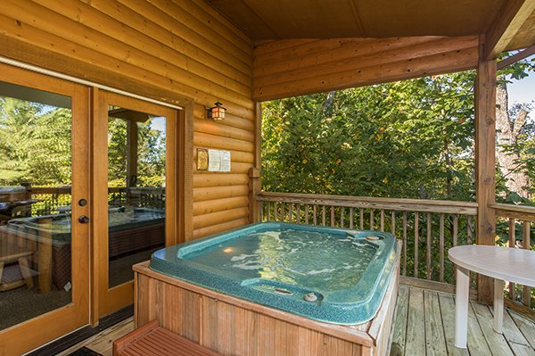 Hot tub on a covered deck at Mountain Valley Hideaway, a 2 bedroom cabin rental located in Pigeon Forge