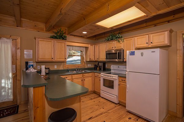 Kitchen with white appliances at Mountain Valley Hideaway, a 2 bedroom cabin rental located in Pigeon Forge