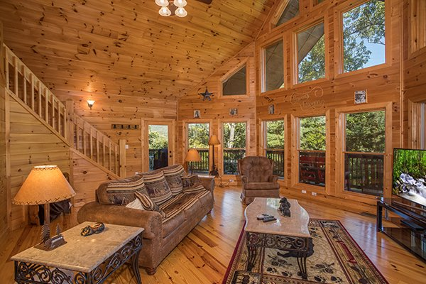 Living room with vaulted ceiling and large windows at Mountain Valley Hideaway, a 2 bedroom cabin rental located in Pigeon Forge