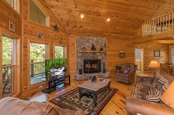 Fireplace, TV, and lots of windows in the living room at Mountain Valley Hideaway, a 2 bedroom cabin rental located in Pigeon Forge