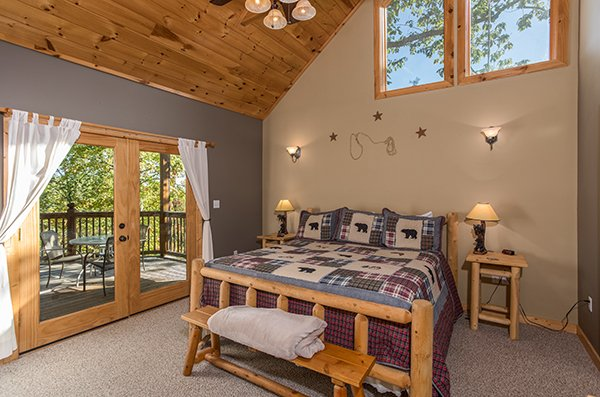 Loft bedroom with a king bed and deck access at Mountain Valley Hideaway, a 2 bedroom cabin rental located in Pigeon Forge