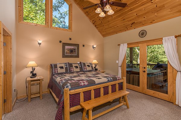 Bedroom with king log bed and deck access at Mountain Valley Hideaway, a 2 bedroom cabin rental located in Pigeon Forge