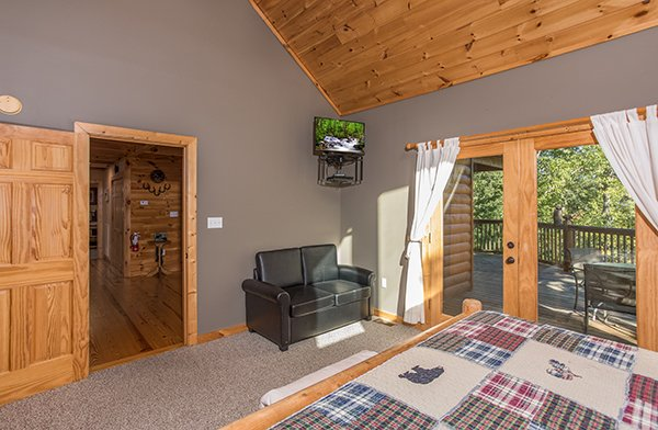 Bedroom with a loveseat, TV, and deck access at Mountain Valley Hideaway, a 2 bedroom cabin rental located in Pigeon Forge
