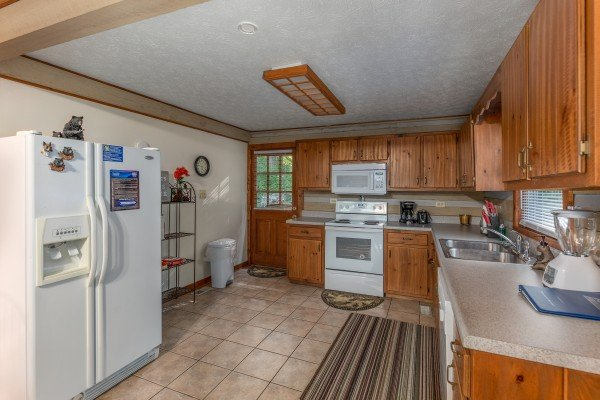 Kitchen with white appliances at Cabin by the Creekside, a 4 bedroom cabin rental located in Pigeon Forge