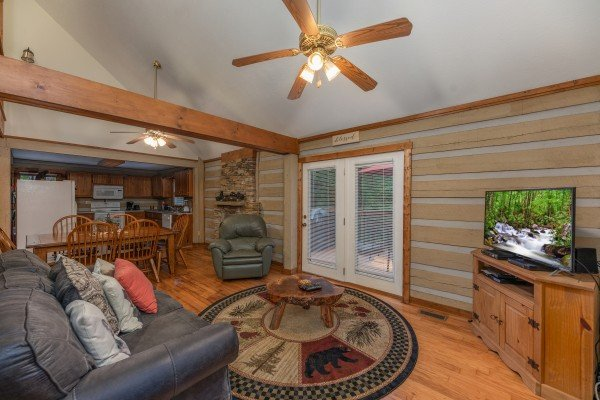 Living room with TV and dining room at Cabin by the Creekside, a 4 bedroom cabin rental located in Pigeon Forge